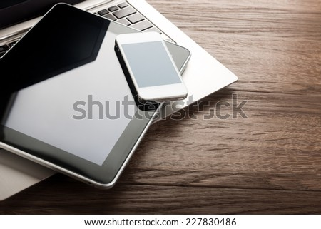 keyboard with  phone and tablet pc on wooden desk - stock photo