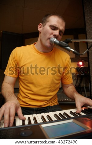 keyboarder is playing and singing - stock photo