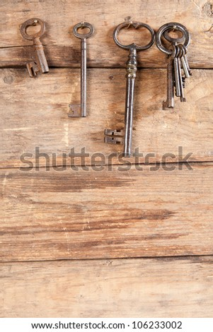 Keyring and rusty keys hanging on a wooden background - stock photo