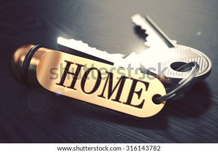 Keys and Golden Keyring with the Word Home over Black Wooden Table with Blur Effect. Toned Image. - stock photo
