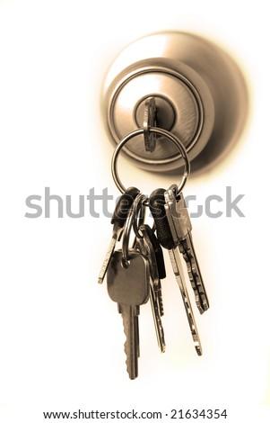 Keys in lock hanging from door knob - stock photo