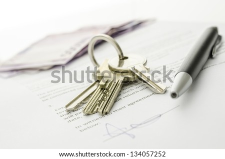 Keys of a new house on a signed contract of house sale with money in background. Concept of closed deal. - stock photo