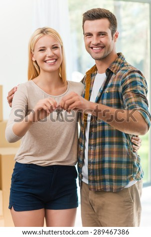 Keys of our new life together. Beautiful young loving couple holding keys and smiling while standing in their new house - stock photo