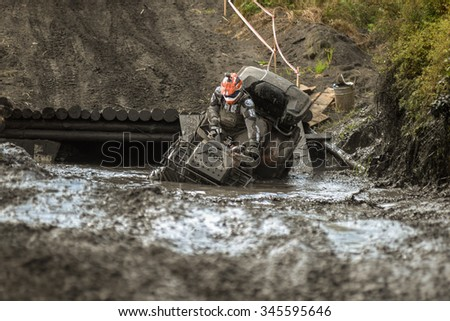 "KHABAROVSK RUSSIAN - SEPTEMBER 12 : An unidentified rider in action at The stage of the Khabarovsk enduro ""Drive trofy on September 12, 2015 in Khabarovsk Russia"" ATV through the mud with big splash"