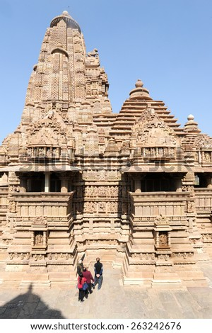 Khajuraho, India - 30 January 2015: People climb to the hindu temple on UNESCO World Heritage Site, Khajuraho Group of Monuments built between 950 and 1150