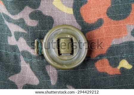 Khaki button on the fabric with a camouflage pattern. Background. - stock photo