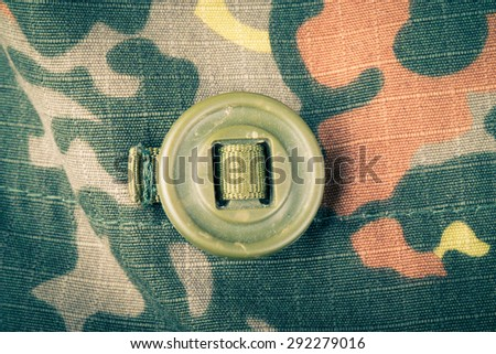 Khaki button on the fabric with a camouflage pattern. Background. Toned. - stock photo