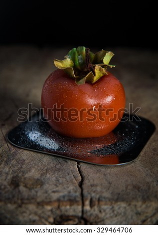 Khaki persimmon fruit on metal dish with droplets on rustic cutting board - stock photo