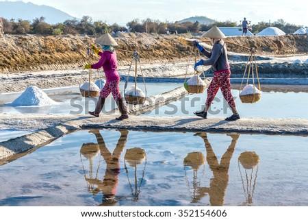 Khanh Hoa, Vietnam, June 30th, 2015: Farmers carrying salt on embankment with full shoulders  alignment salt burden hurried mirror into water create beauty in peasant labor Khanh Hoa, Vietnam - stock photo
