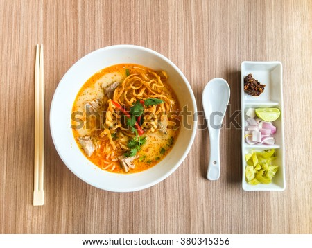 Khao Soi Thai Noodle Curry Soup with chicken on wood table, top view. - stock photo