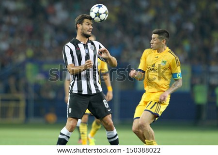 KHARKIV, UKRAINE -AUG 07:Tziolis(L) of PAOK  in action with Sosa(R) of METALIST  during the UEFA Champions League soccer match METALIST vs PAOK at Metalist Arena on August 07,2013 in Kharkiv, Ukraine. - stock photo