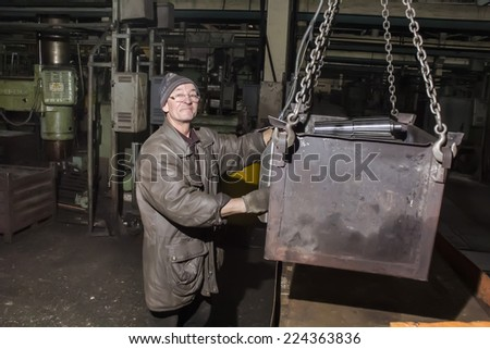 Kharkov, UKRAINE - 7 November 2013: Kharkiv Tractor Plant. in the production of the employee performs his work. Man moves cargo
