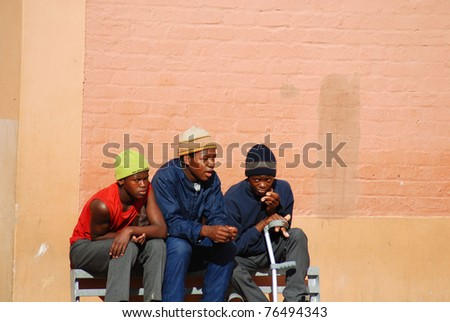KHAYELITSHA, CAPE TOWN - MAY 22 : A unidentified group of young teenagers sit on the side of a street in Khayelitsha township, on May 22, 2007, Cape Town, South Africa - stock photo