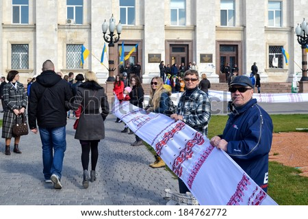 KHERSON, UKRAINE - MARCH 30, 2014: people unfold extremely long Ukrainian traditional embroidered by hand towel to integrity of Ukraine and to 70th jubilee of institution of Kherson region. - stock photo