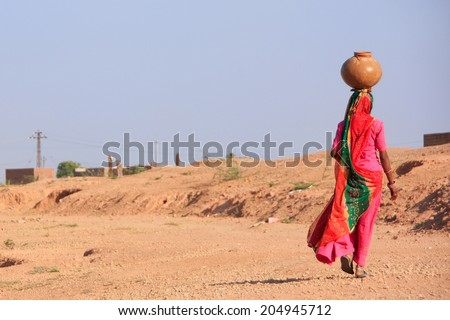 KHICHAN, INDIA - FEBRUARY 12: An unidentified woman carries jar with water on her head on February 12, 2011 in Khichan, India. Village of Khichan is famous for feeding flocks of wintering crains. - stock photo