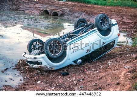 KhonKaen - Thailand - January 1, 2016: Car flipped over off the road after a collision. Scene of an accident caused by the high speed and the road made treacherous in KhonKaen, Thailand. - stock photo