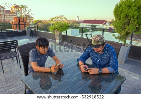 Khonkean,Thailand - December 6, 2016 : Asian young men using the mobile phones on wood table