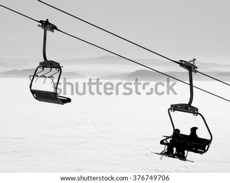 ki lift chairs on winter day over the clouds, cableway funicular chair equipment sport skiing background /  silhouette of skiers on mountain hill - stock photo