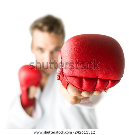 Kick boxer with red boxing gloves performing a martial arts punch. Isolated  over white background. - stock photo