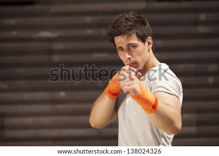 Kick boxing athlete training some punch (selective focus) - stock photo