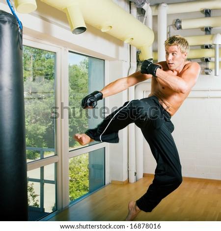 Kickboxer kicking the sandbag - stock photo