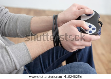 kid addicted by video-game playing with hands blocked by wired controller - stock photo