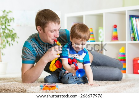 kid and his dad play musical toys at home