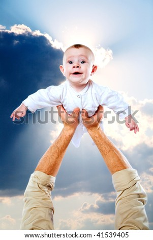 Kid and his father's hand against the cloudy sky - stock photo