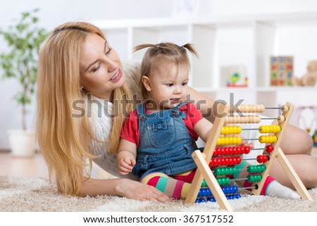 kid and mother playing with abacus - stock photo