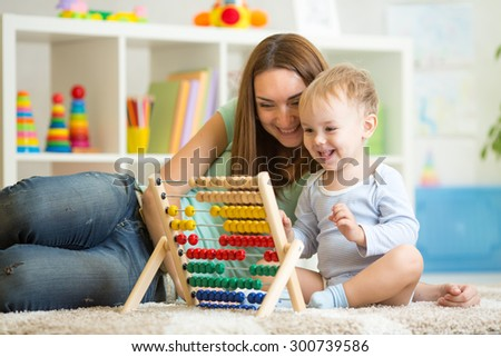 kid and mother playing with abacus at home - stock photo