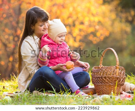 kid and mother sit with apples basket outdoors in autumnal park - stock photo