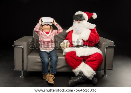 Kid and Santa Claus wearing virtual reality headsets while sitting on sofa isolated on black