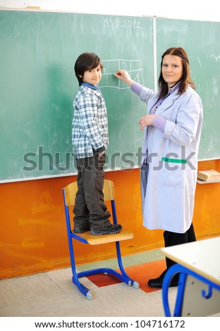 Kid and teacher in classroom - stock photo