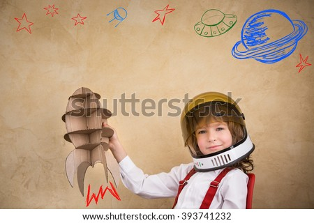 Kid astronaut with cardboard toy rocket. Child playing at home. Earth day concept - stock photo