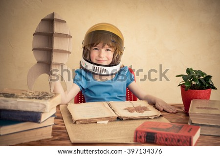 Kid astronaut with cardboard toy rocket. Child playing at home. Earth day 2016 concept - stock photo