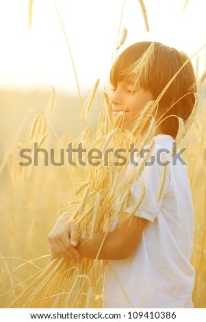 Kid at wheat field hugging harvest grain - stock photo
