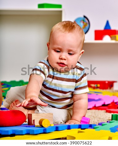 Kid baby boy lying on floor and plying with puzzle toy.  Early baby development. - stock photo
