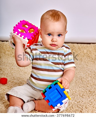 Kid baby boy sitting on floor and plying with puzzle toy at home.  - stock photo