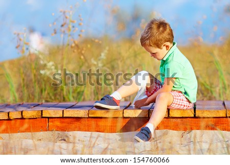 kid bandaging injured leg - stock photo