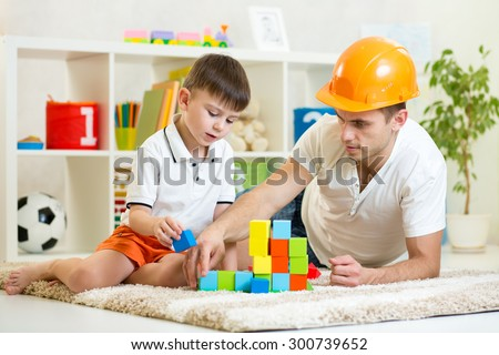 kid boy and father play builders in nursery at home - stock photo