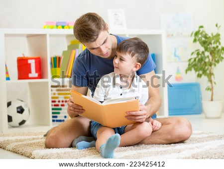 kid boy and his father read a book on floor at home - stock photo