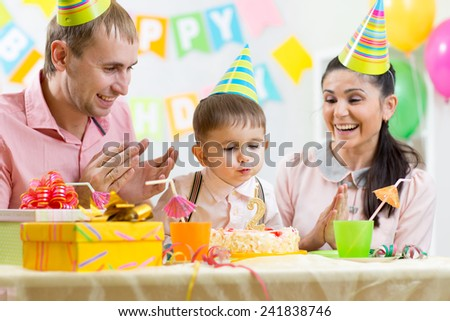 kid boy blowing candle on birthday cake - stock photo