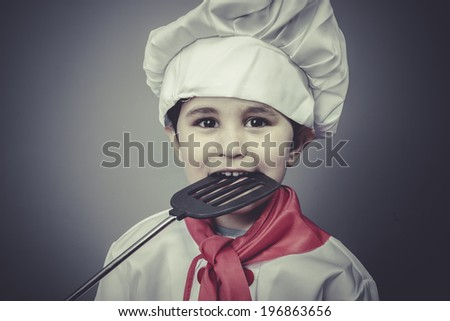 kid, boy dressed as a cook with kitchen utensils - stock photo