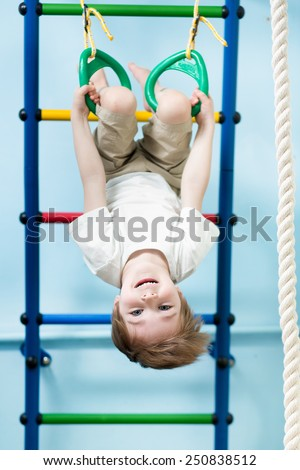 kid boy hanging on gymnastic rings at home - stock photo