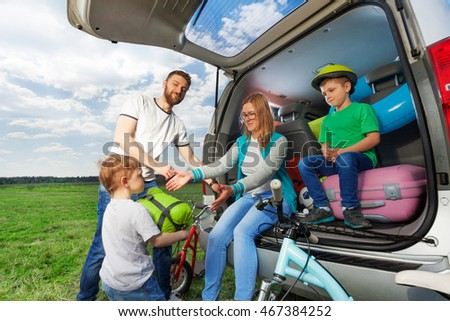 Kid boy helping his parents to load their car boot