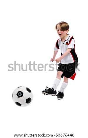 Kid / Boy in complete german soccer outfit shoots a bal - stock photo