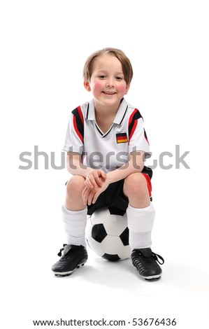 Kid / Boy in complete german soccer outfit sitting on a football - stock photo