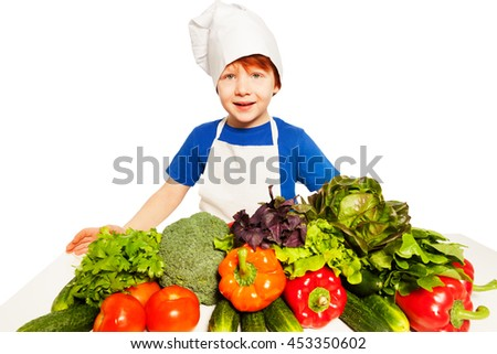 Kid boy in cook's uniform preparing a healthy meal - stock photo