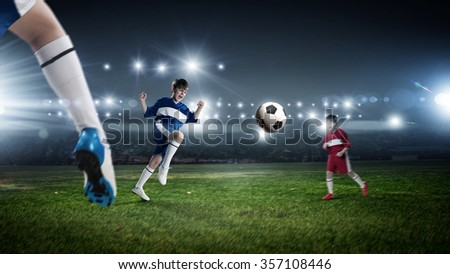 Kid boy in red uniform on soccer stadium kicking ball - stock photo