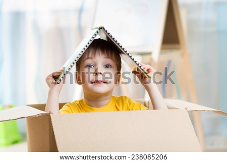 kid boy playing in a toy house in children room - stock photo